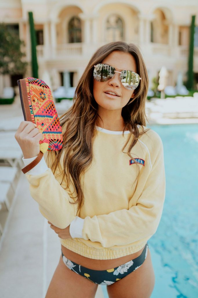 yellow RVCA sweatshirt, Rylie floral bikini, and nena and co clutch